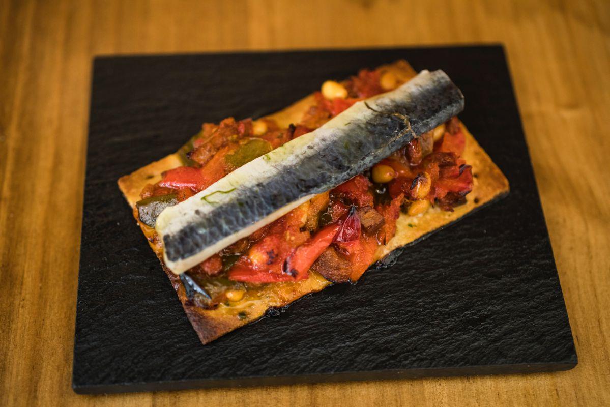 Tapa de Coca de 'titaina' con sardina marinada del restaurante Tofolet, en Valencia.