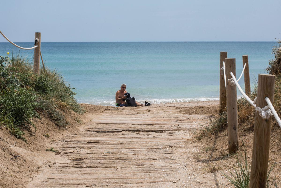 Un hombre toma el sol a la orilla de la playa en El Saler (Parque Natural La Albufera, Valencia).