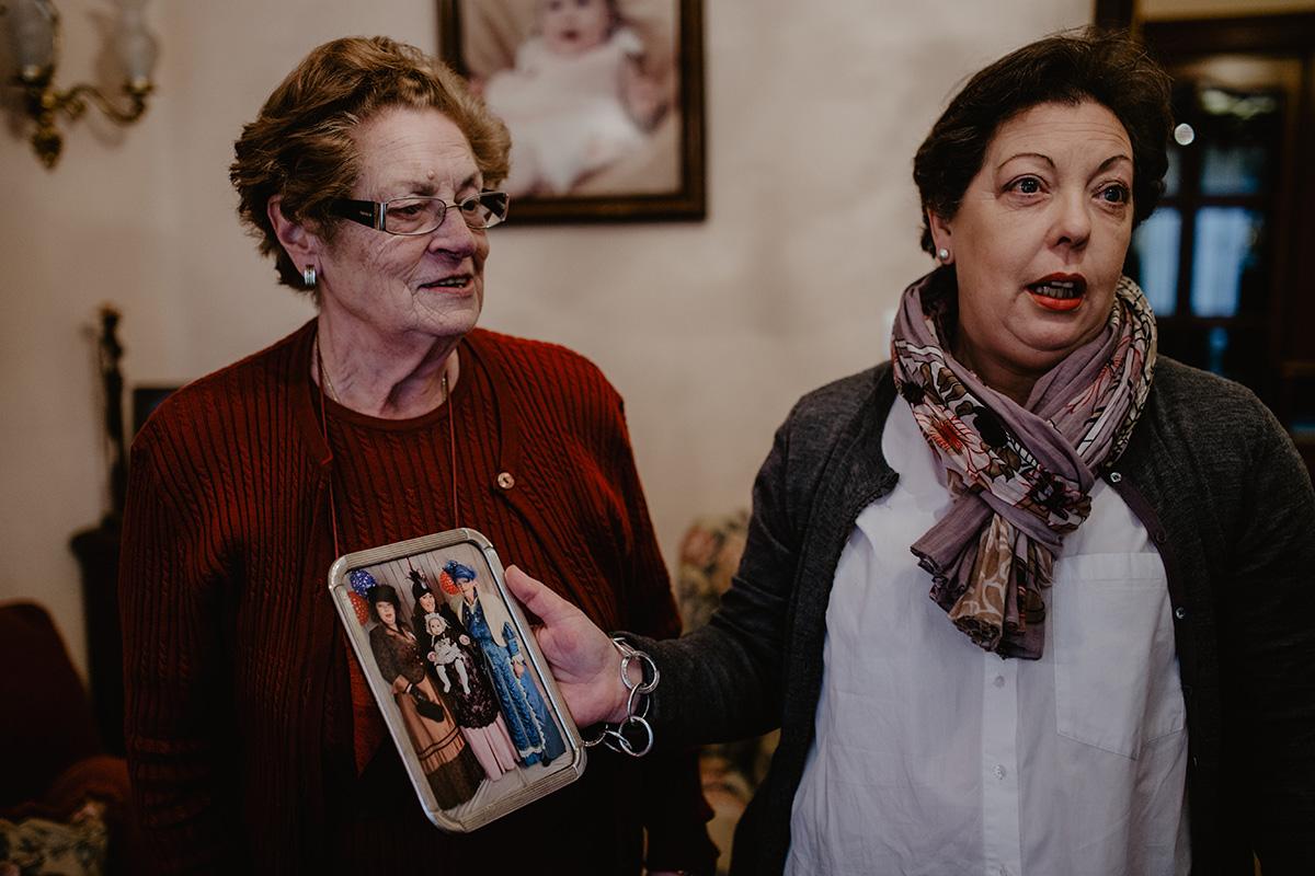 María y Gloria, en el salón de esta última, muestran una foto con las cuatro generaciones de viudas.