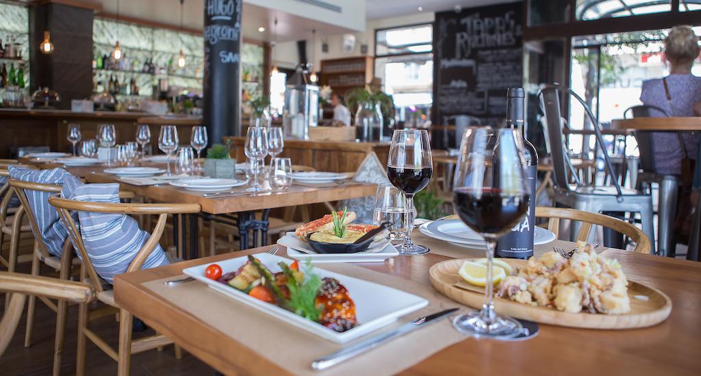 Restaurante del Hostal Cuba con mesas con comida y vinos