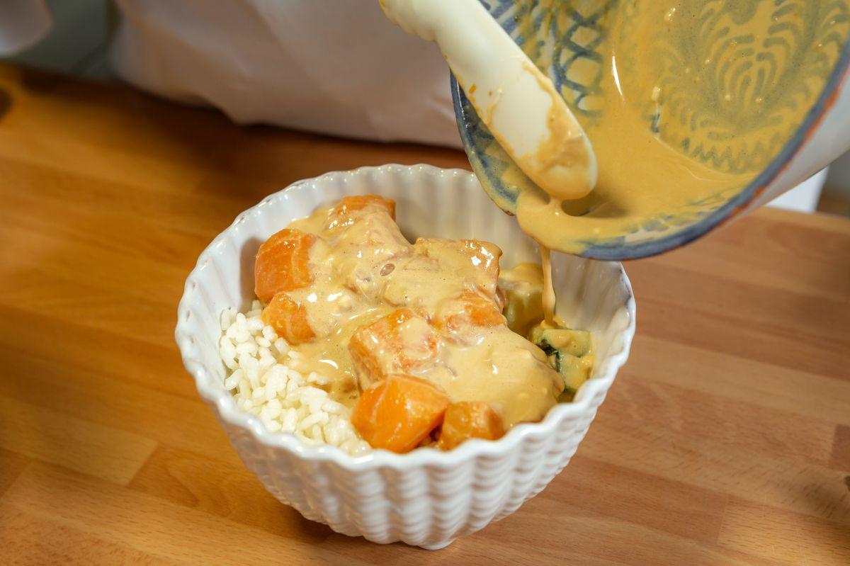 Vertiendo la salsa sobre el poke bowl de salmón.