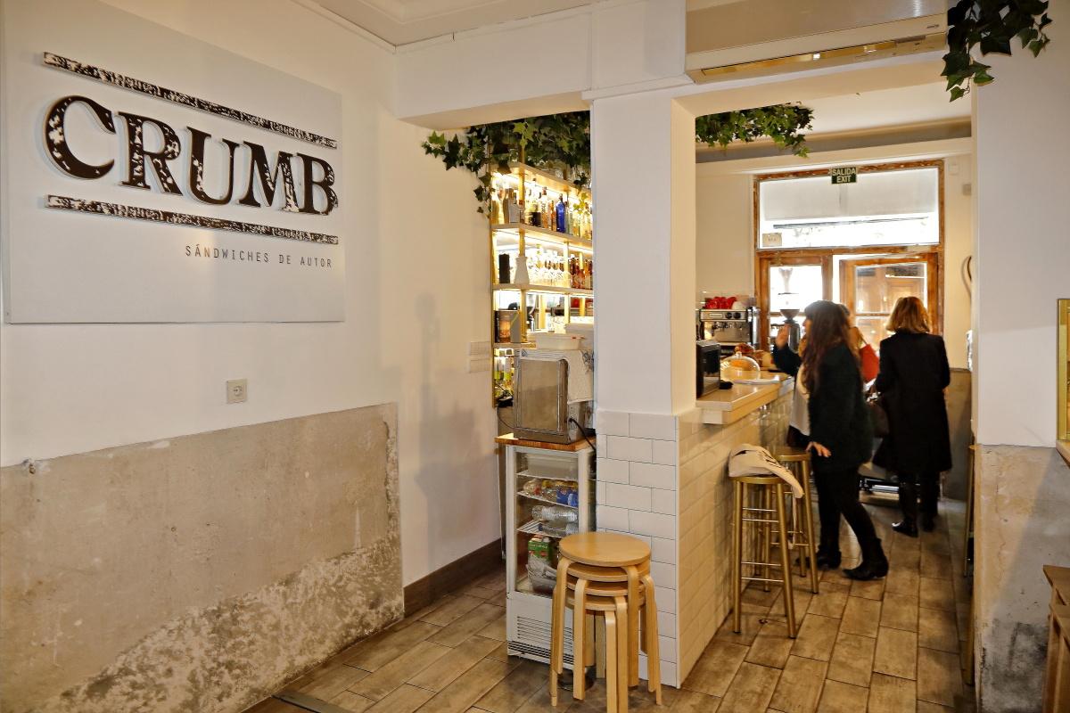 Vista del interior de la sandwichería 'Crumb', en Madrid, y del ambiente de los clientes en la barra del local.