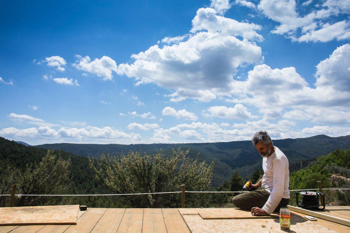 Aberto Ruiz, propietario de la casa rural 'Mar de la Carrasca', en el parque natural de Peñagolosa, Castellón, arregla la tarima para la práctica de yoga con vistas al valle.