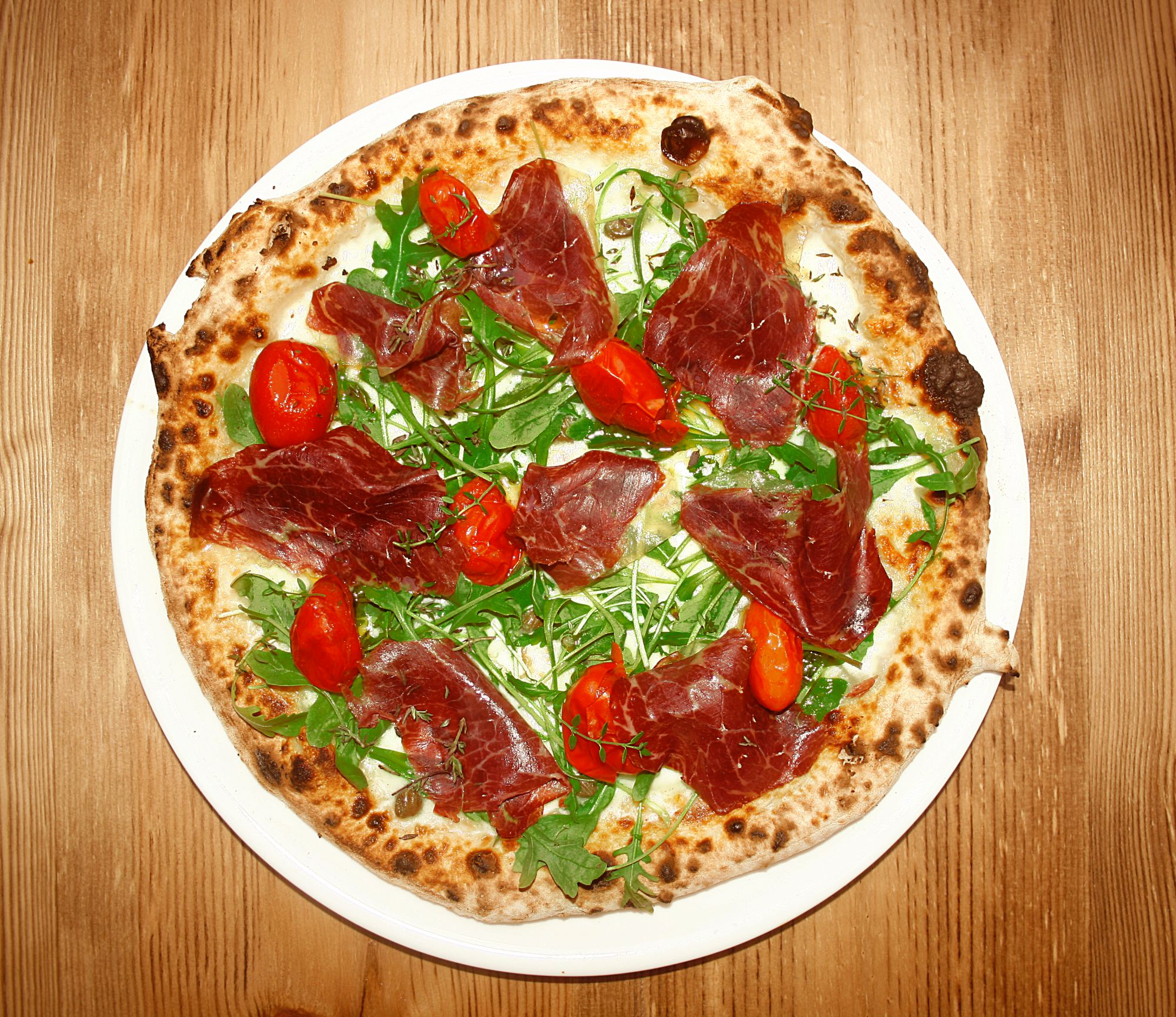 Pizza de cecina, 'mozzarella', rúcula, alcaparras y tomatito confitado de 'Garden Pizza'. Foto: Garden Pizza.