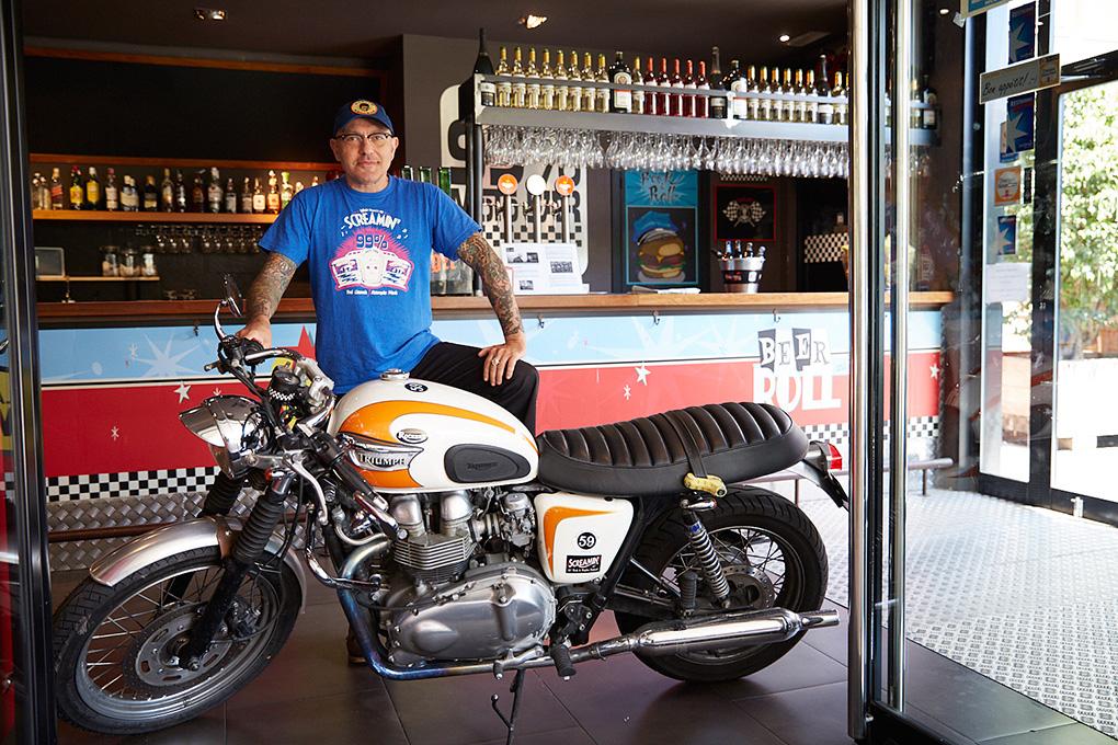 Jordi Bou, propietario del 99% Moto Bar, con su moto Triumph.