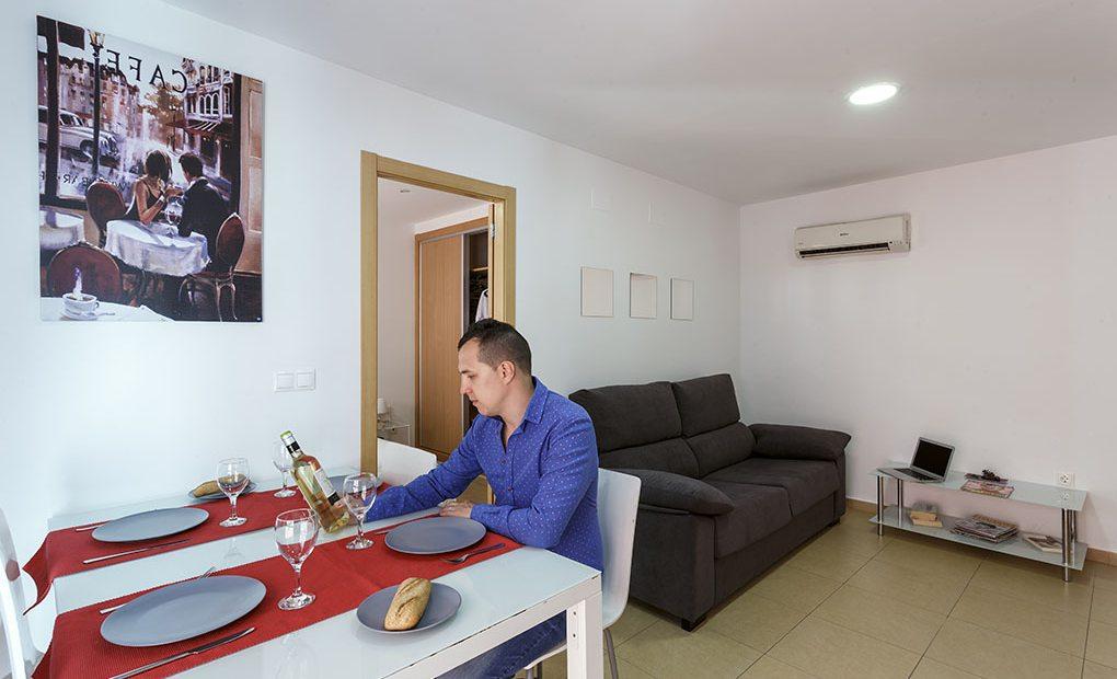 En la sala hay un sofá cama, un señor sentado en la mesa comedor mirando una botella de vino y una televisión
