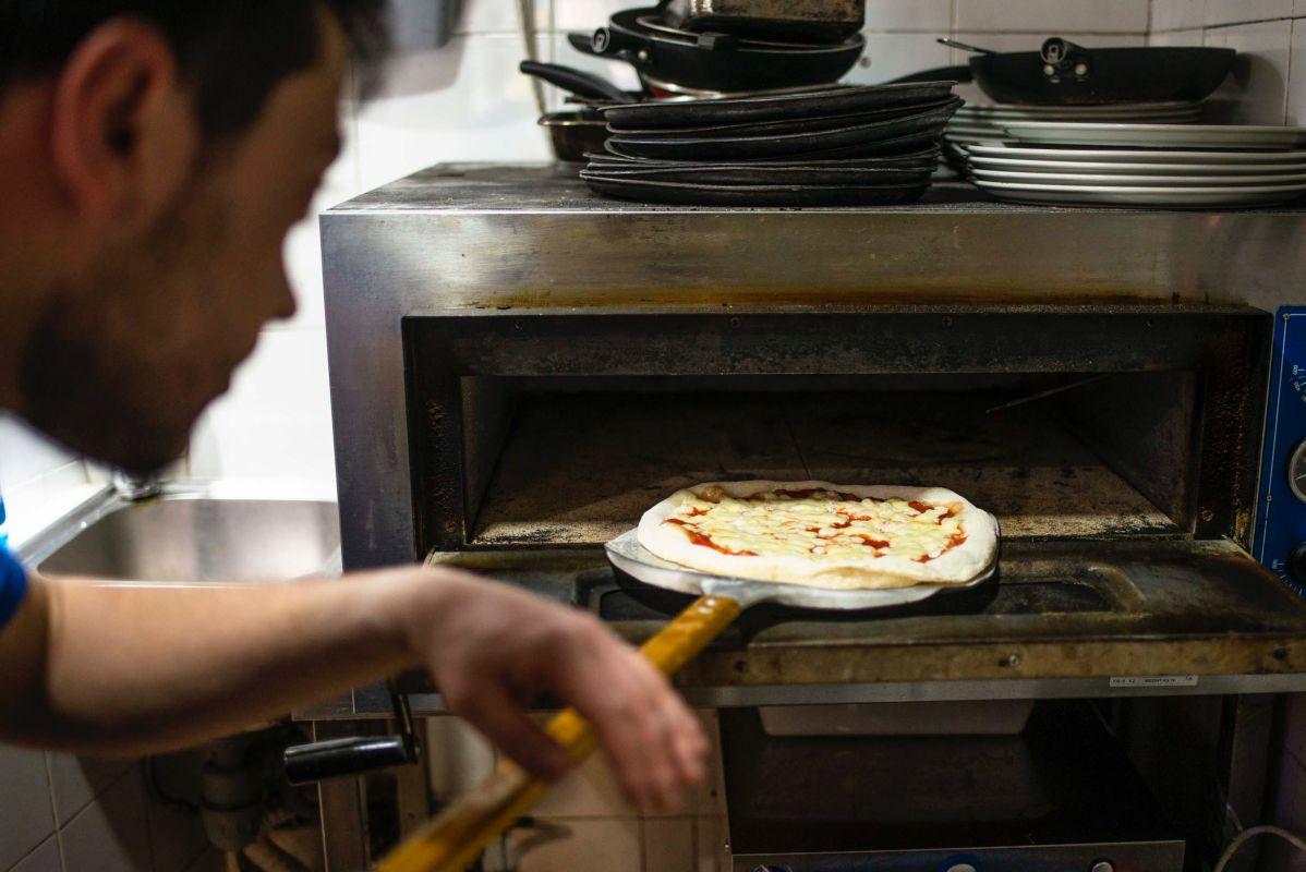 Mikele Corsalini metiendo la pizza margarita en el horno de 'La pizza è bella', en Madrid.
