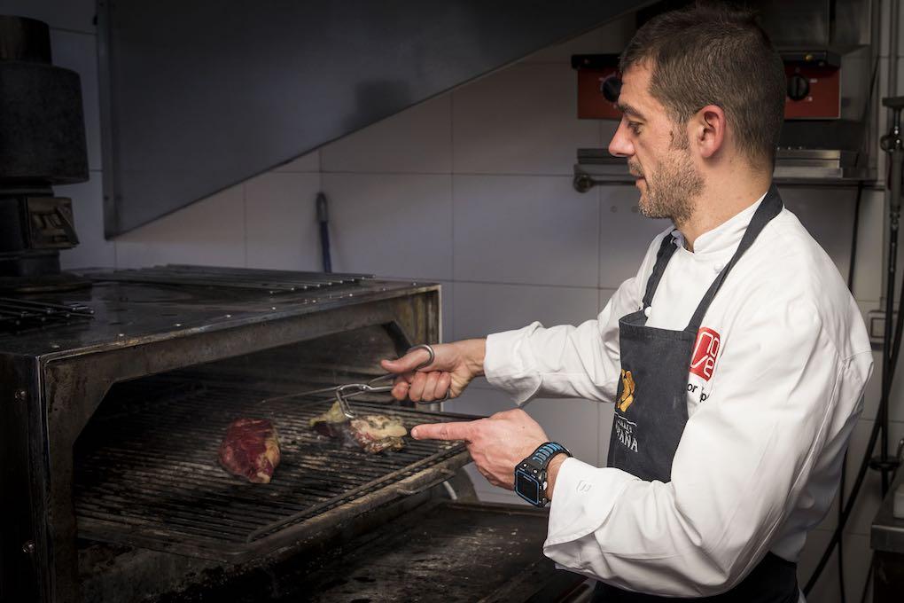 Héctor López cocinando carne de buey a la brasa