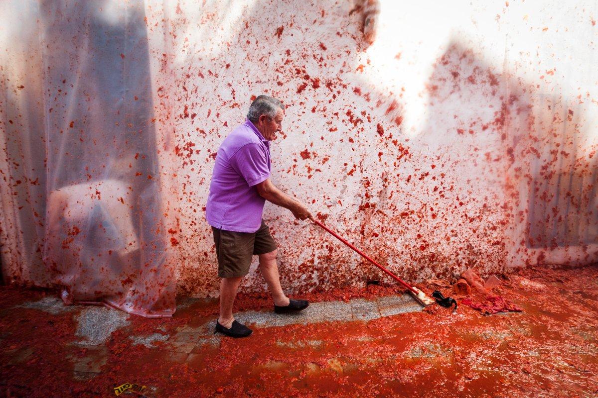 Es hora de la limpieza. Los vecinos barren las calles teñidos de rojo.