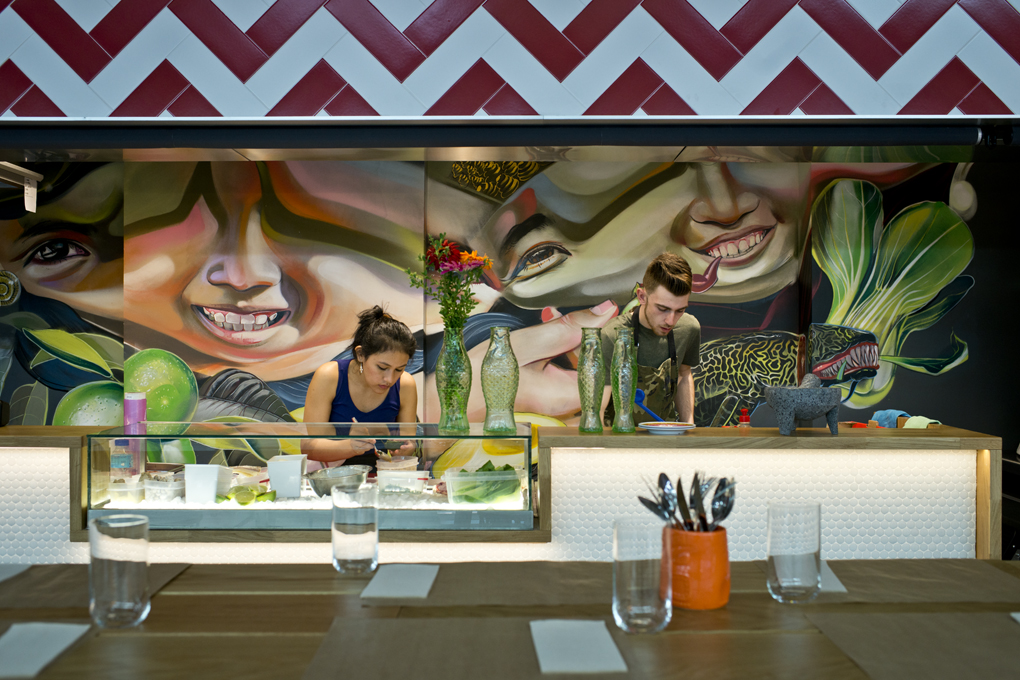 El equipo de Roberto preparando la comanda con el colorido mural que define su cocina al fondo.