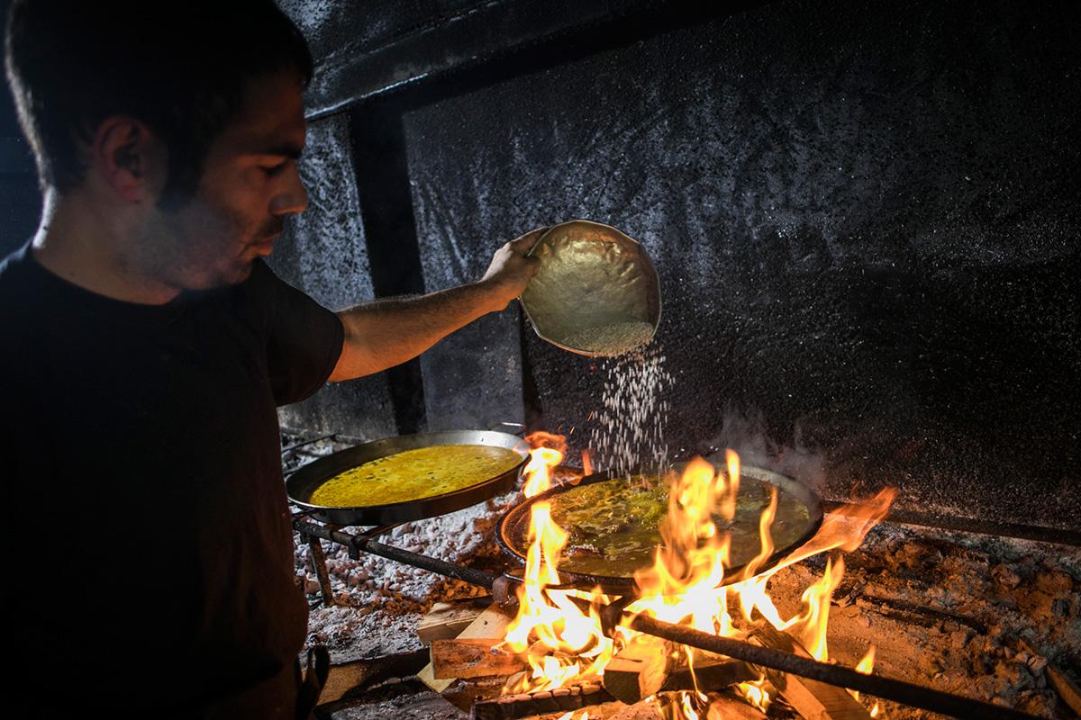 Marcos, a los mandos de las paellas, esparce el arroz que no se tocará hasta pasados 18 minutos.