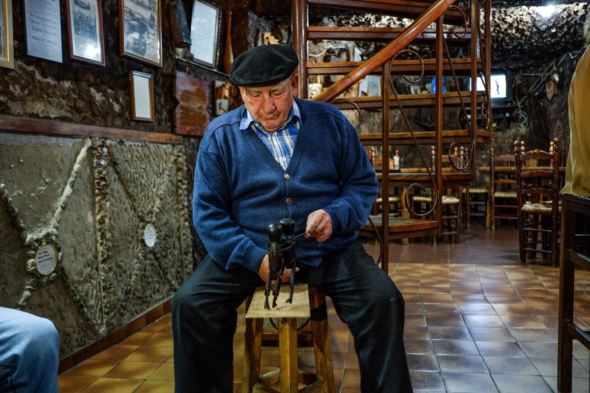 Pedro Cañada, dueño del bar más famoso de Jarandilla, hace bailar con el puño una figuras de madera