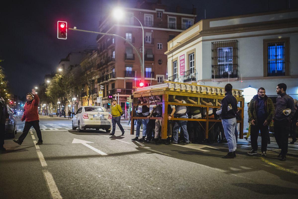 El equipo de capataces de la Hermandad de El Amor controla el tráfico mientras la parihuela cruza la avenida.