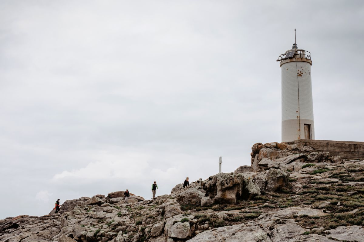 Un grupo de personas se acercan al faro O Camiño dos Faros (Costa da Morte, A Coruña).