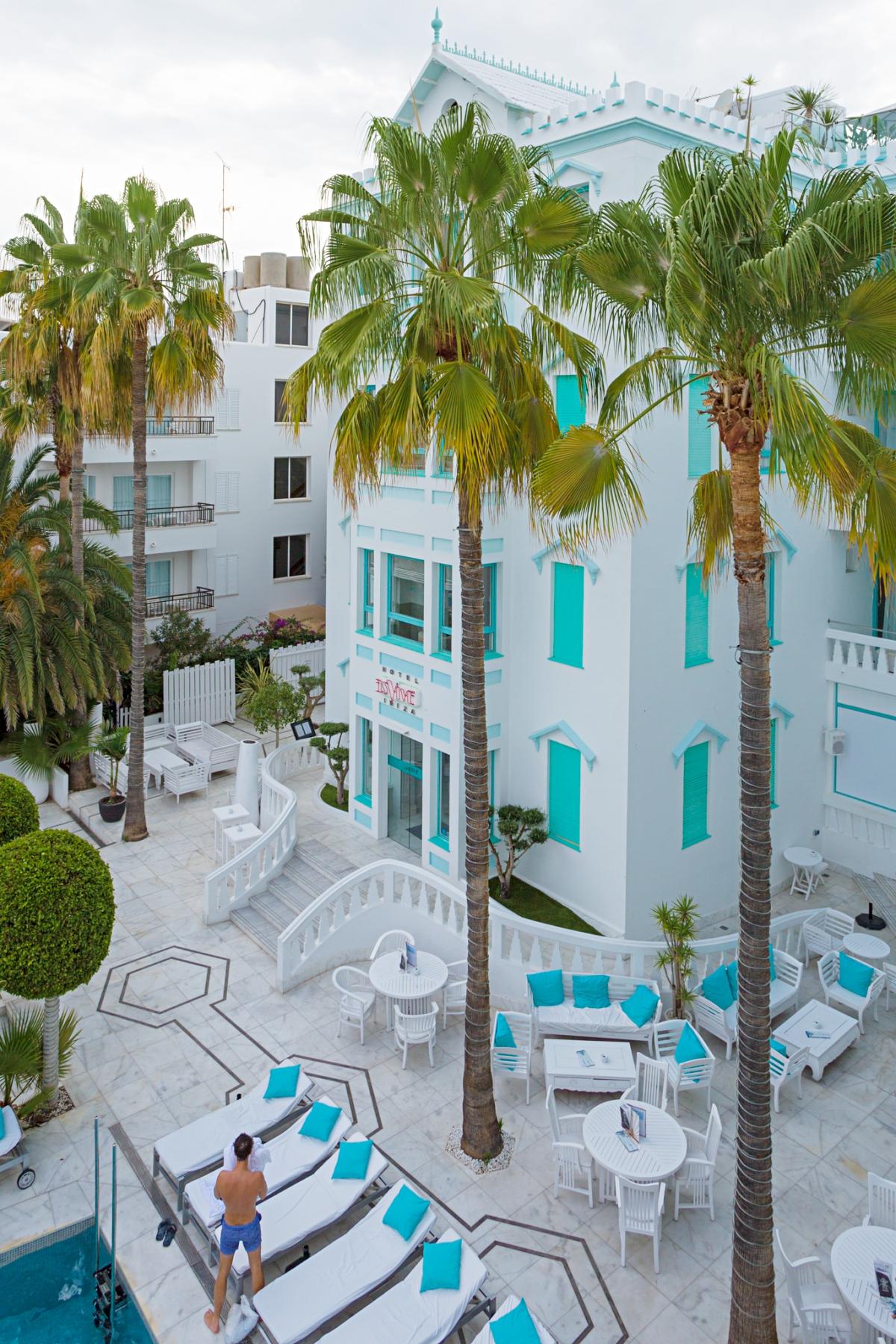 Vista de la fachada blanca y las palmeras del hotel Es Viver (Ibiza).
