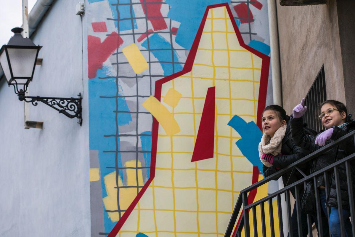 Los niños disfrutando del arte urbano con la obra de Srgr de fondo.