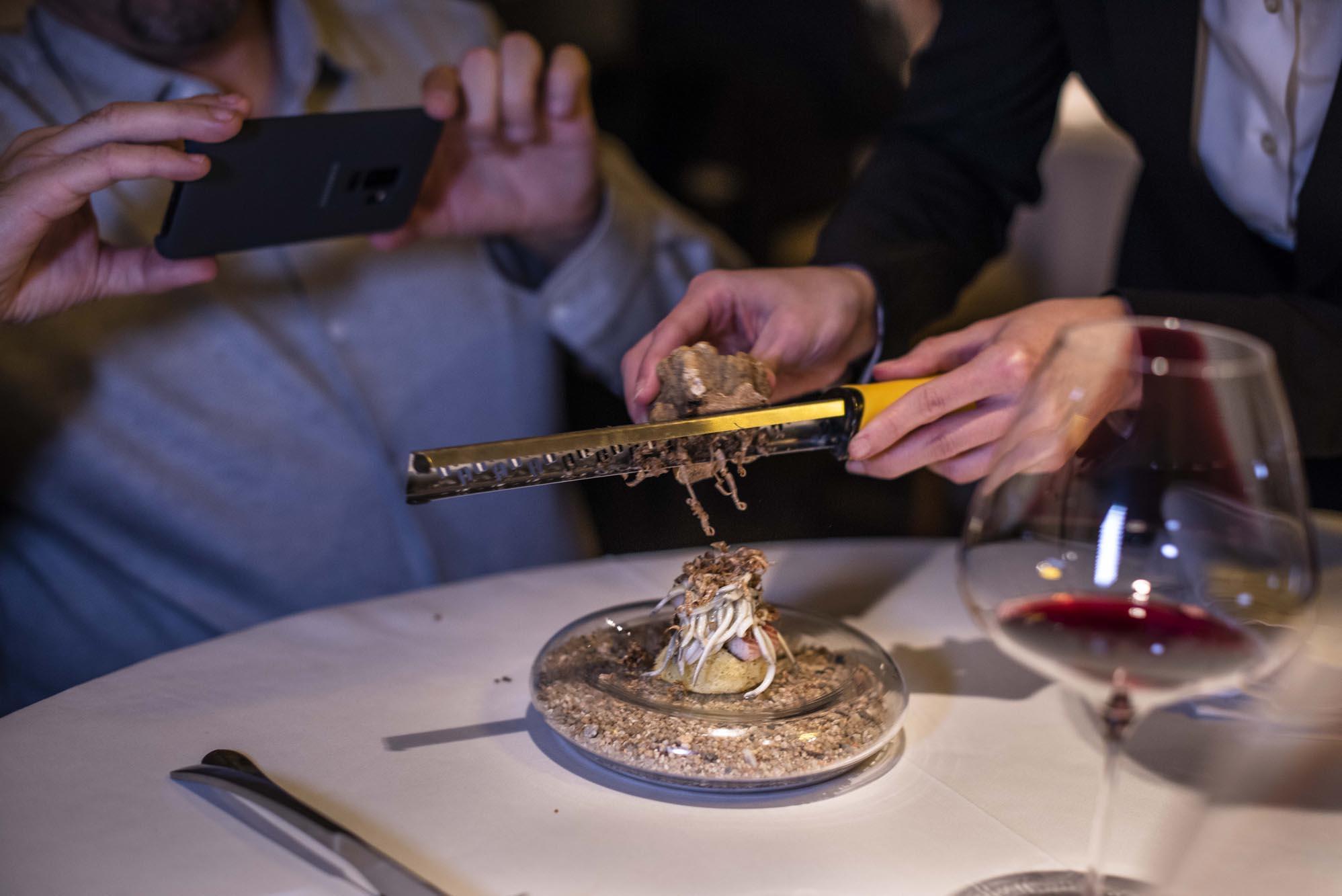 Bizcocho con angulas al natural, pilpil de merluza y anguila ahumada con base de ajo asado y trufa blanca.