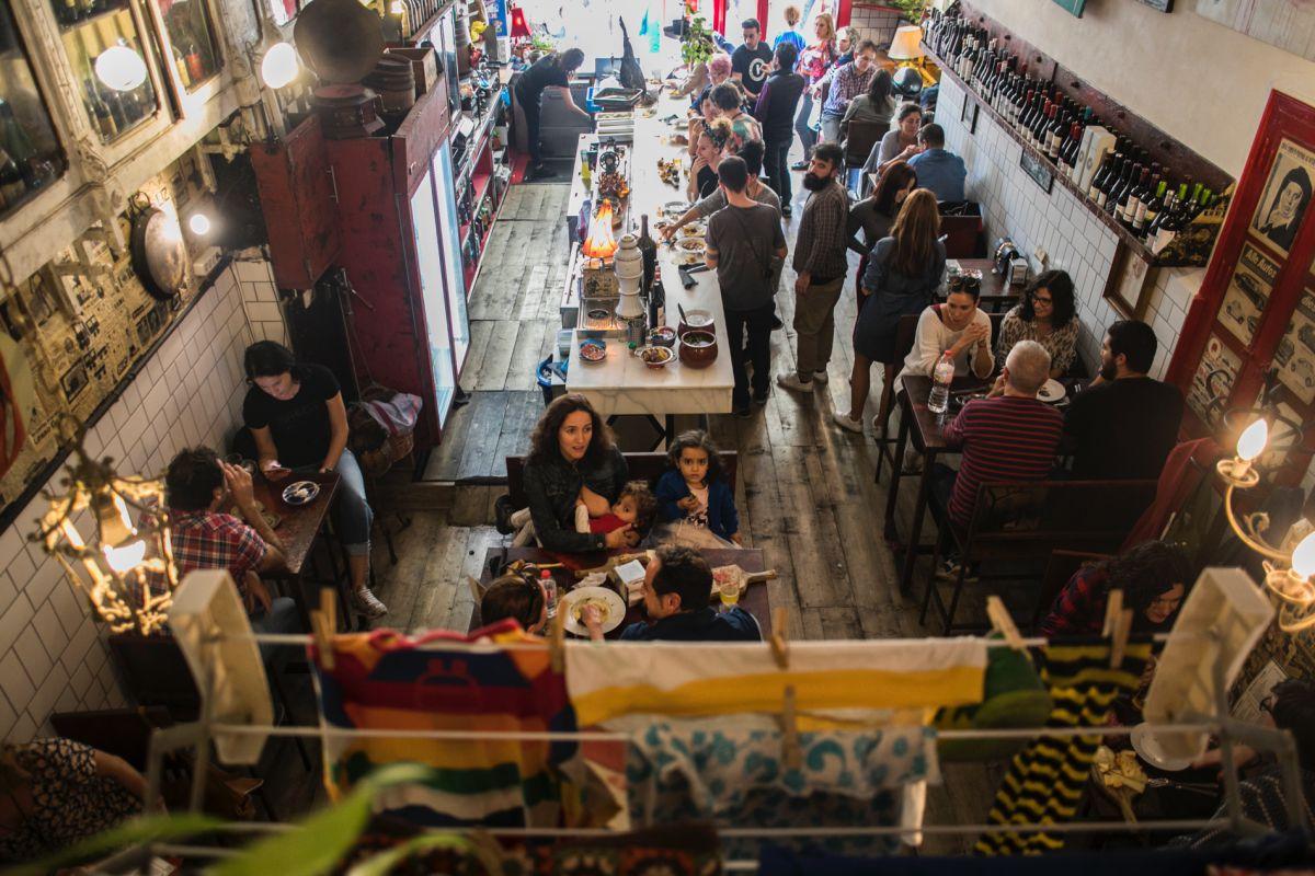Familias, amigos, parejas... se acercan a la 'Bodega La Peseta' para probar su arroz cocinado sobre una calabaza.