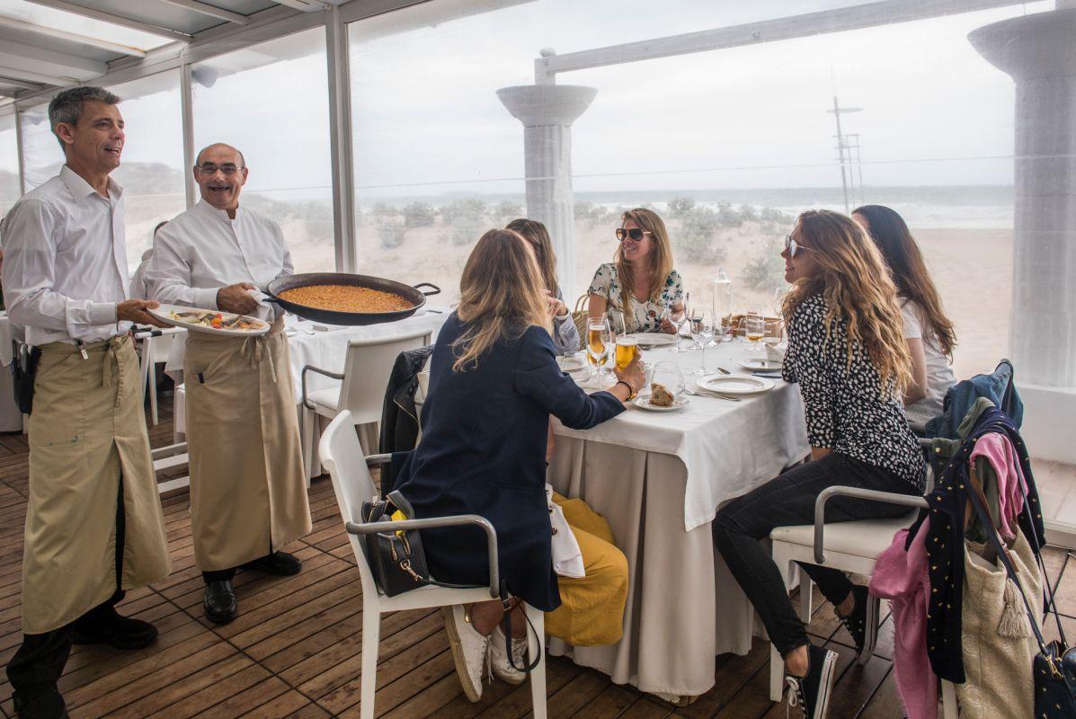 Unos camareros traen la paella a un grupo de amigas en el restaurante 'Arrocería Duna', en El Saler (Parque Natural de La Albufera, Valencia).