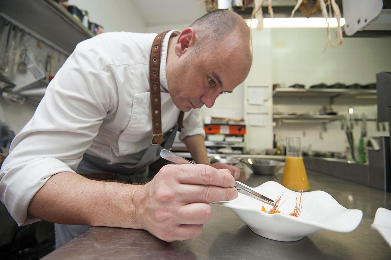Nazario Cano en su cocina emplatando la sopa de galera y alcachofas.