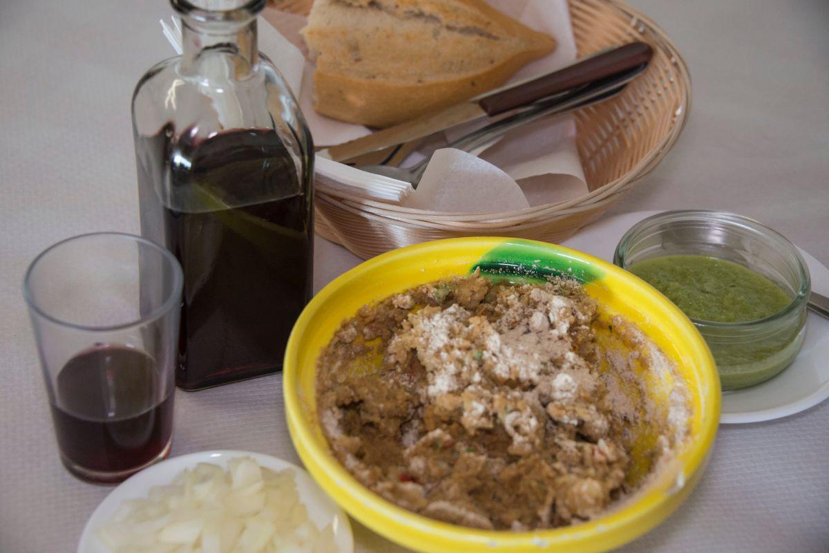 Plato de escaldón de gofio junto al vino en una mesa del guachinche Quintero, en Tenerife.
