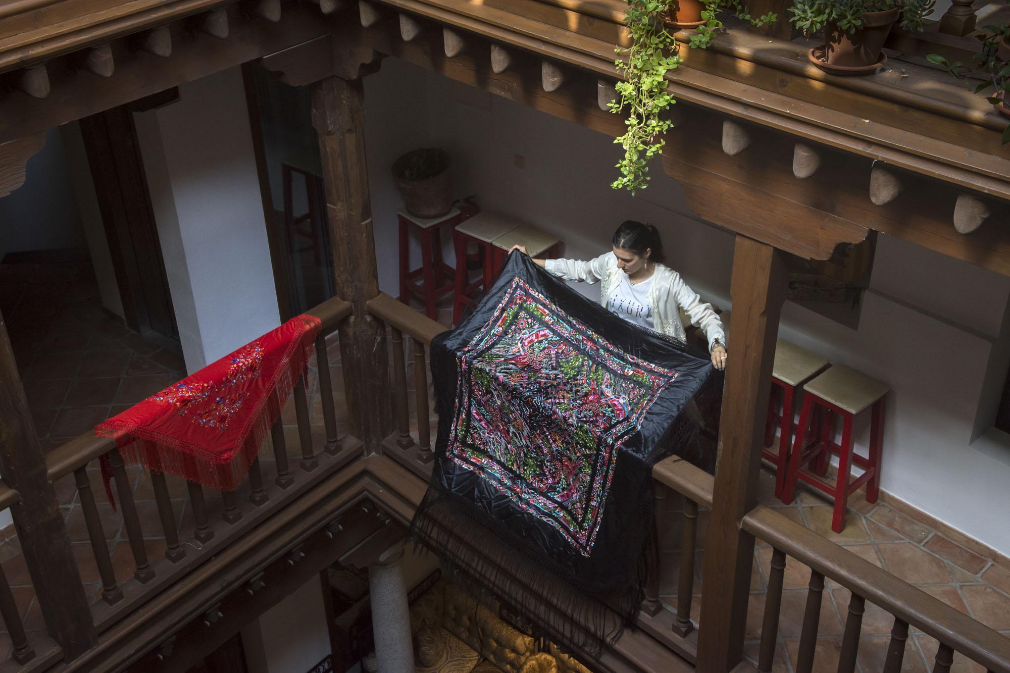 Gabriela, trabajadora del hotel, engalana los corredores del patio con mantones de manila.