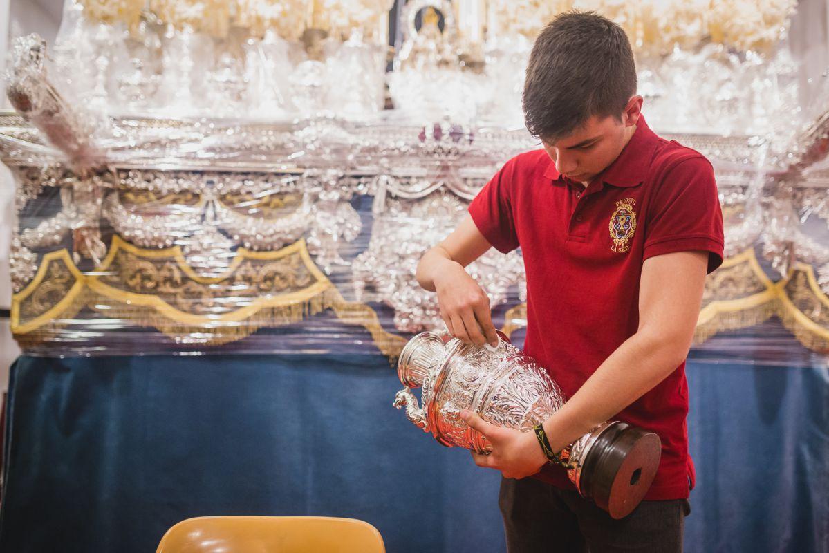 Uno de los jóvenes de la Hermandad de la Sed da lustre a la plata del palio de la Virgen de Consolación.