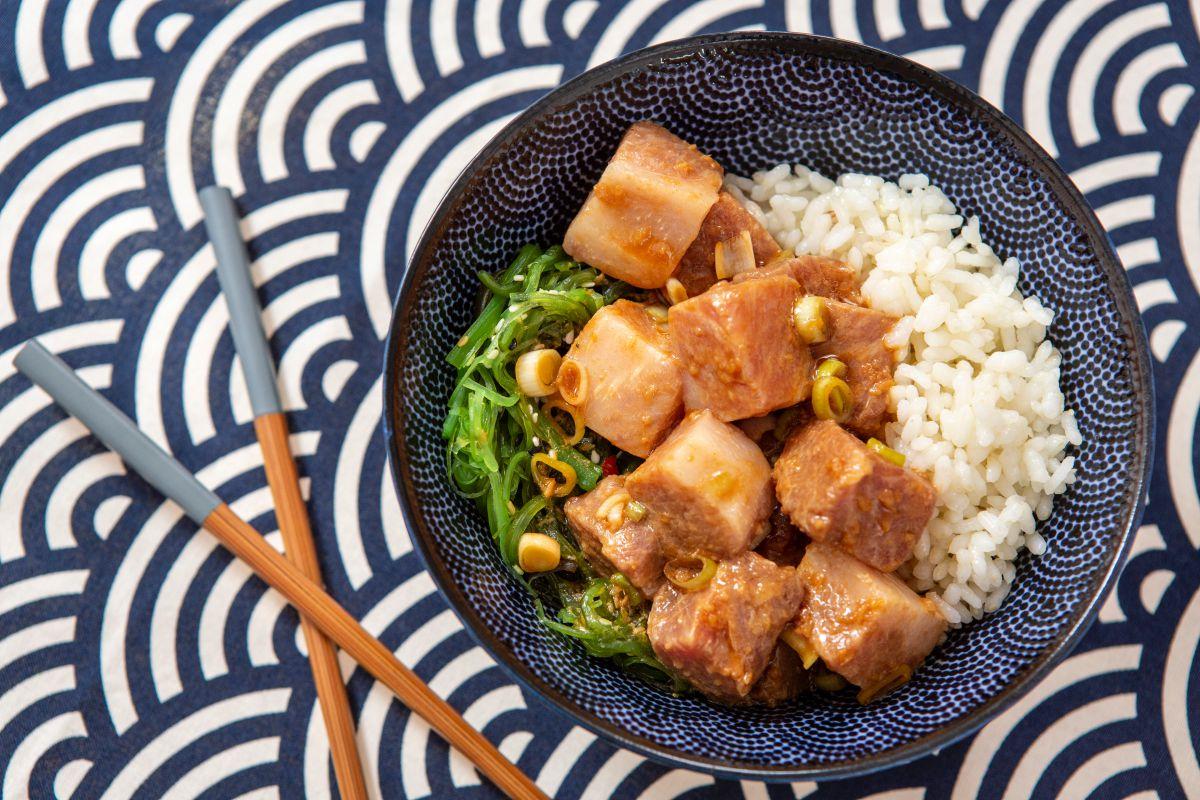 Un poke bowl de atún picante junto a unos palillos chinos listo para comer.