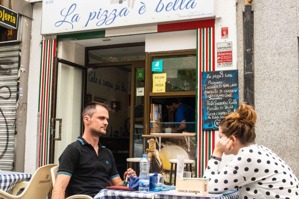 La terraza del 'La pizza è bella', en Madrid, con clientes sentados a sus mesas.