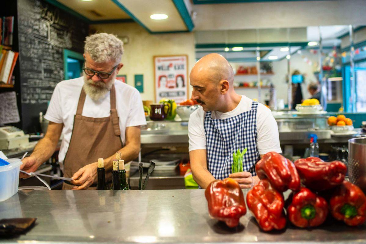 Scott y Fernando, de 'Los Chuchis Bar', en Madrid, preparan el servicio antes de la hora punta.