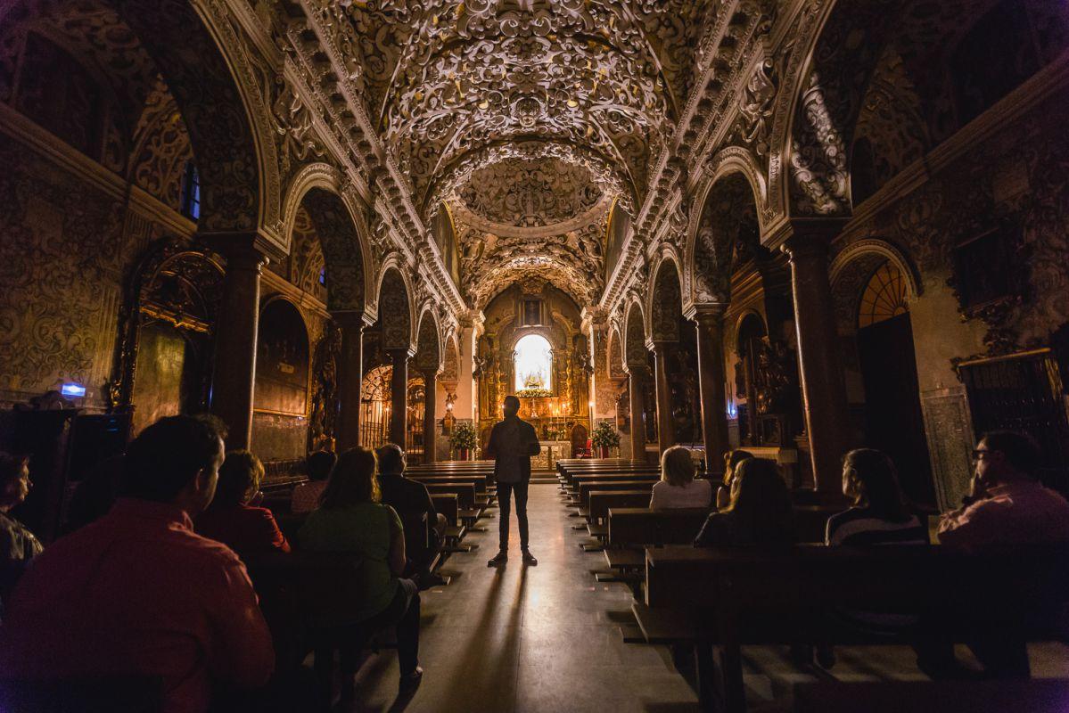 El guía recibe en el interior de la iglesia Santa María La Blanca, de Sevilla, durante la visita nocturna.