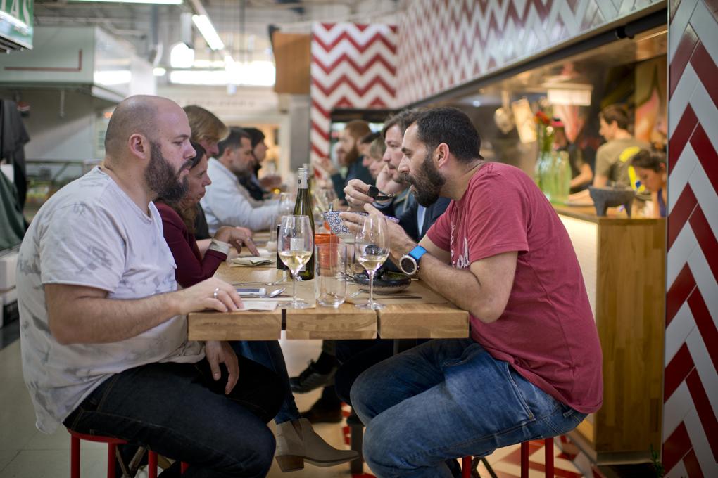 La única mesa con los 16 comensales que caben, impacientes por probar lo que come el de al lado.