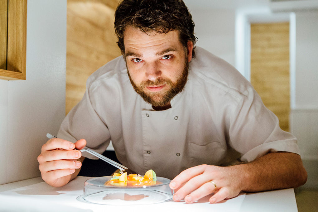 El chef, con un plato de atún escabechado, con puntas de espárrago blanco y raiford
