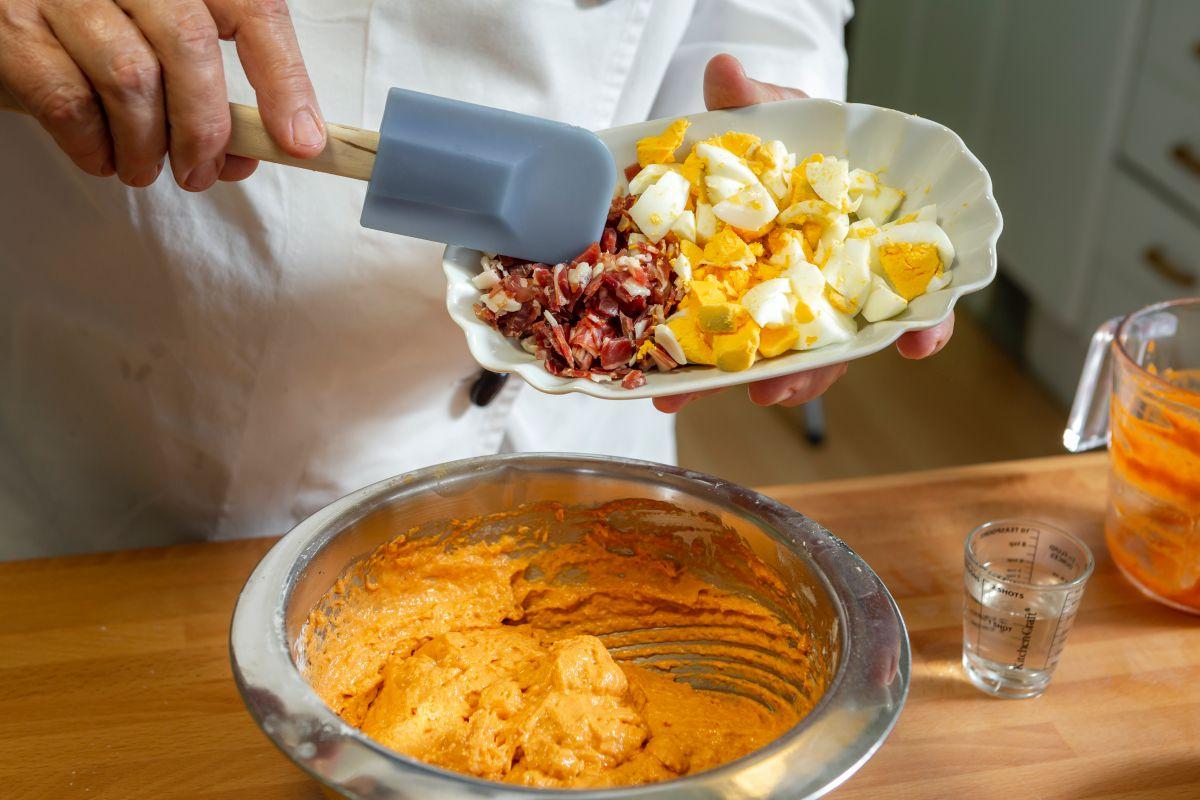 Echando los trocitos de jamón y huevo duro a la masa del bizcocho de salmorejo.