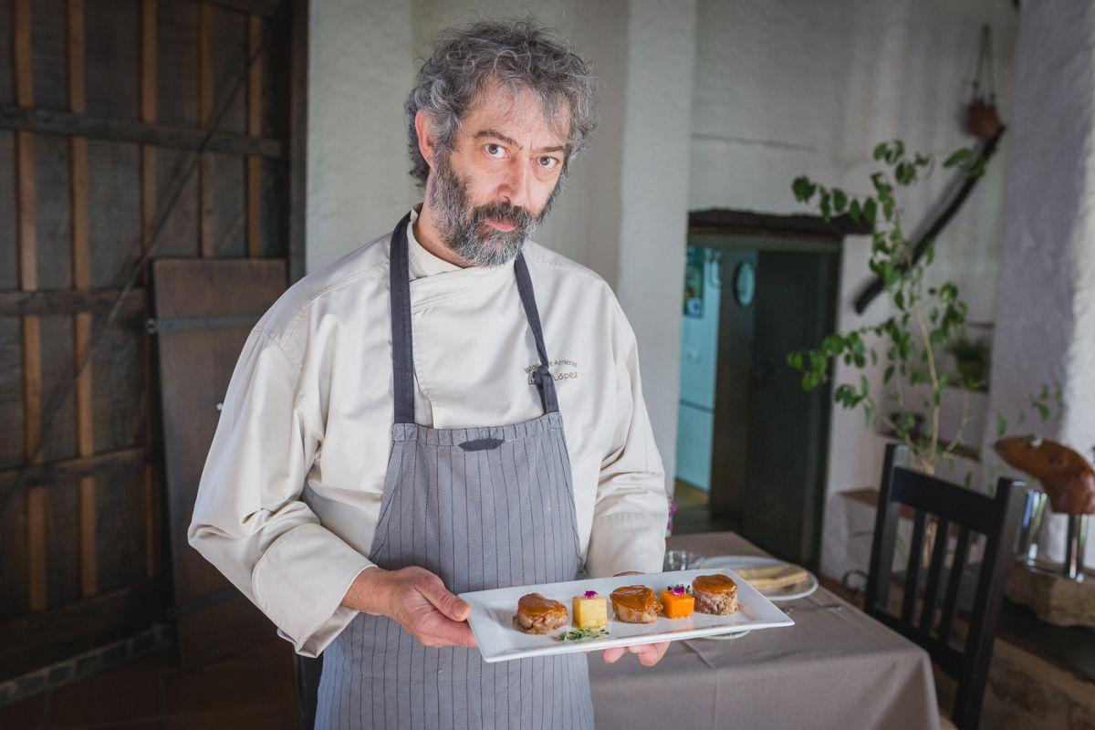 Luismi, del restaurante Arrieros, en Linares de la Sierra, con uno de sus platos a base de cerdo ibérico, en el Parque Natural Sierra de Aracena y Picos de Aroche, Huelva.