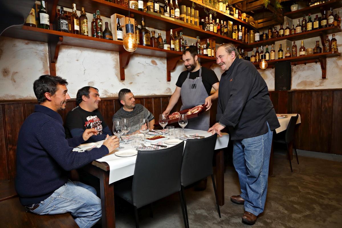 Matías Gorrotxategi y uno de sus hijos muestran el género a los comensales de una mesa en 'Casa Julián'.