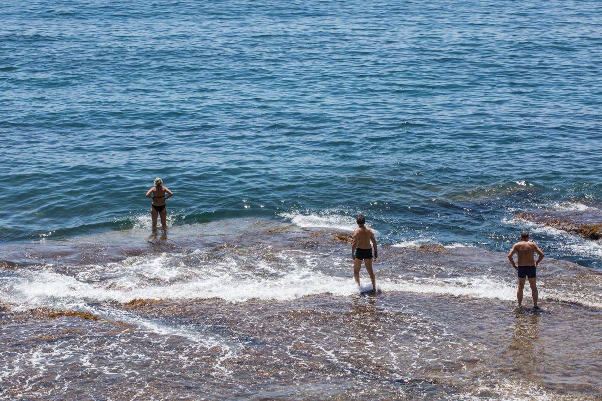 Gente bañándose en la orilla de la cala Mallorquín, en Calpe, Alicante.