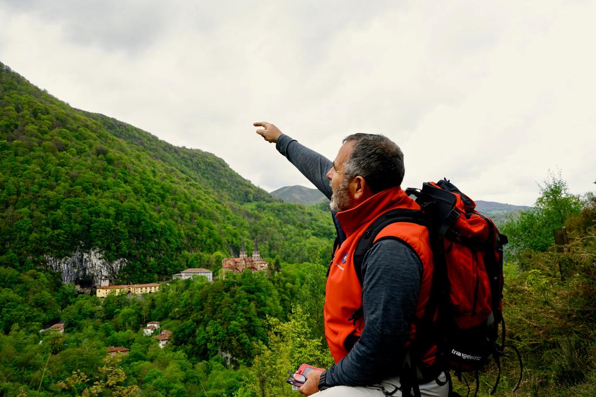El guía Fernando Ruiz señala el monte Auseva desde el de la Cruz de Priena. Al fondo, Covadonga.
