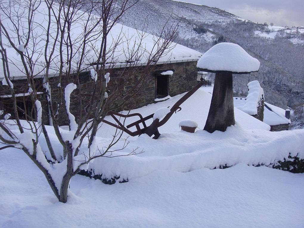 Imagen de una casa rural cubierta y rodeada por nieve