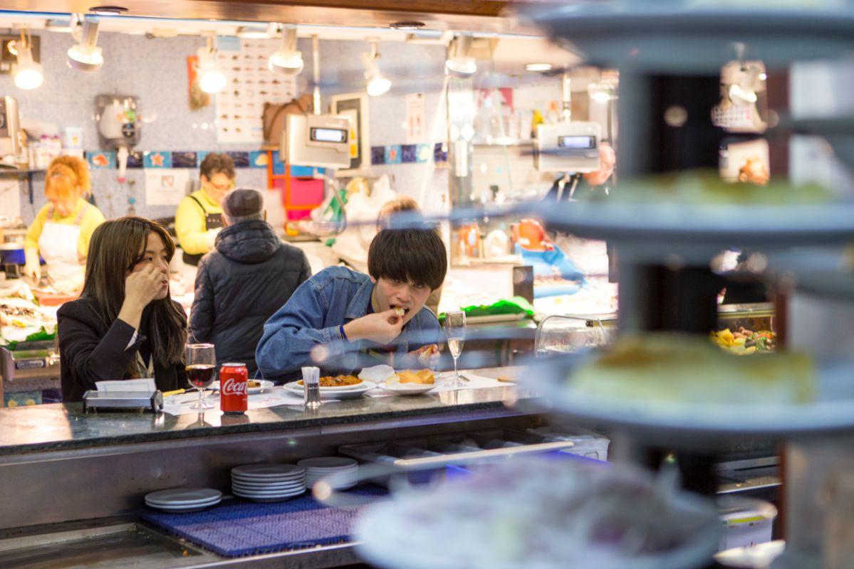 Una pareja de japoneses disfrutando de la ración de caracoles.