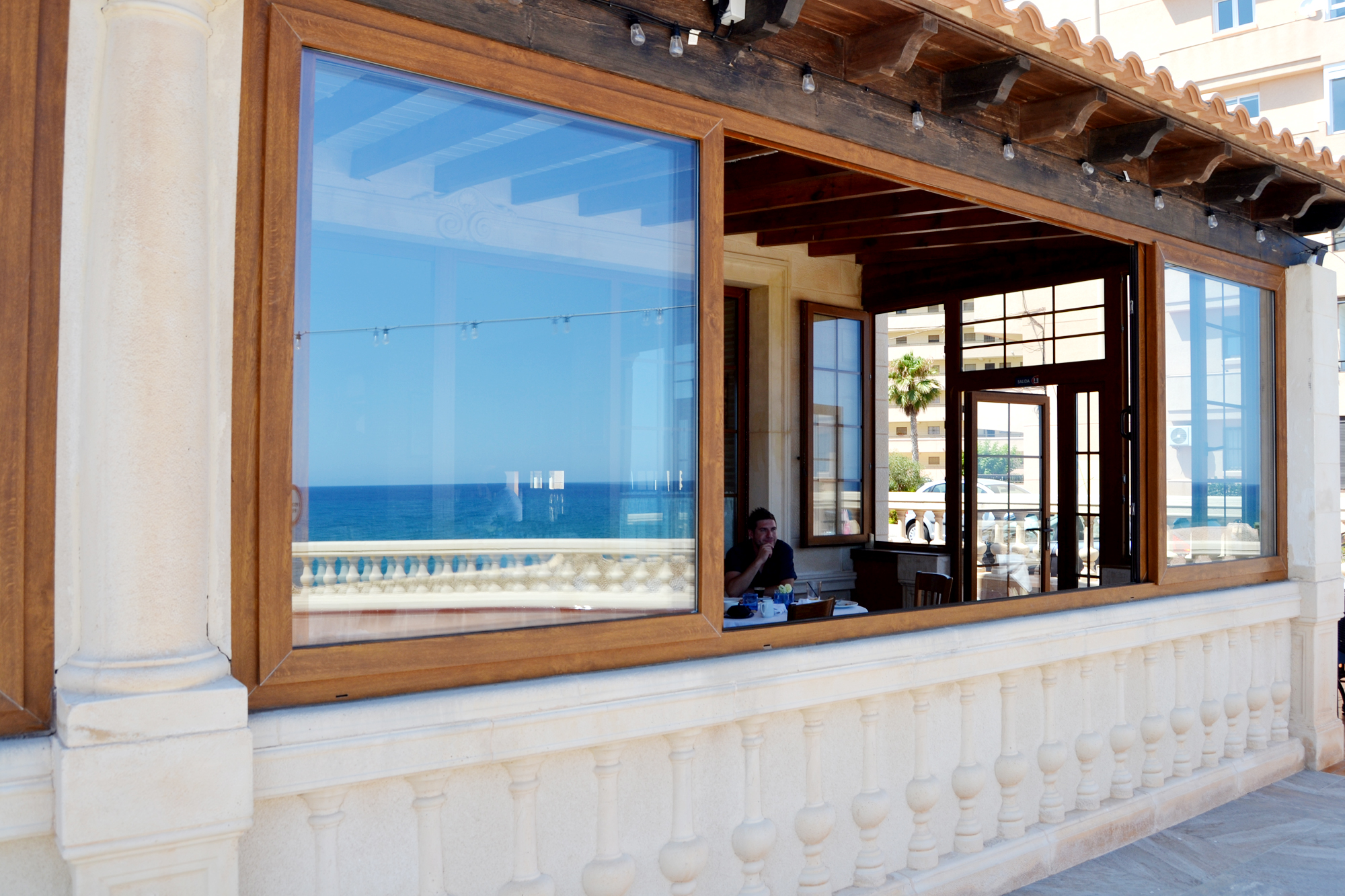 La terraza cubierta. En su reflejo, la terraza al aire libre y las vistas. Foto: A.M.