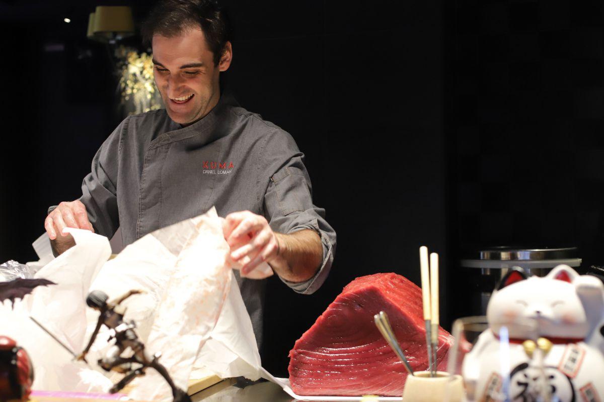 Daniel Lomana manipulando papel secante junto a una imponente pieza de atún rojo.