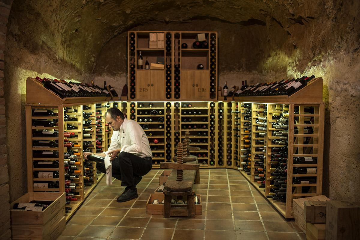 Ramón eligiendo un vino en la bodega, de cientos de años de antiguedad y sobre la que se construyó el restaurante.