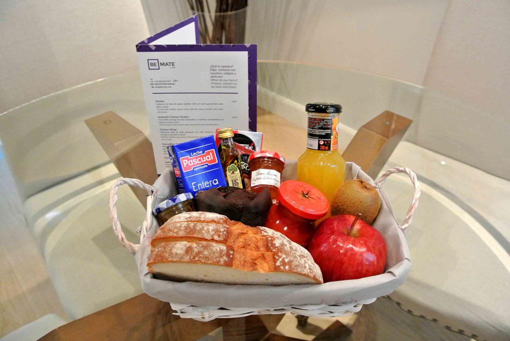 Cesta para desayunar compuesta por pan, leche, fruta, zumos y mermeladas