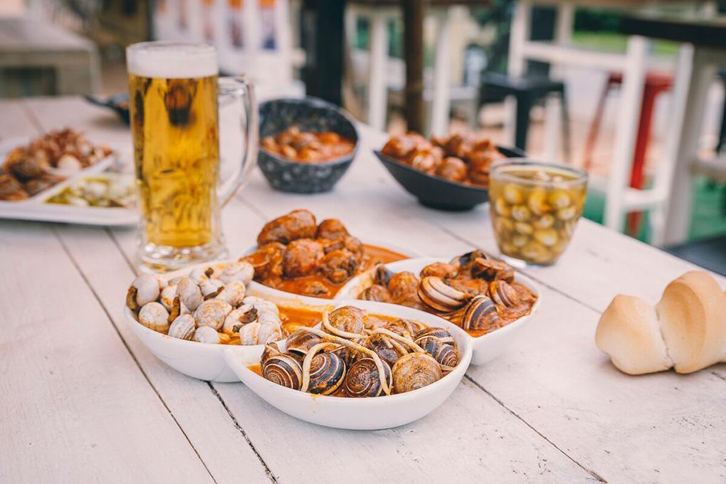 Plato degustación de Noreña con cabrillas con gulas, con rabo de toro, caracoles al picantón y gordos con salsa tradicional.