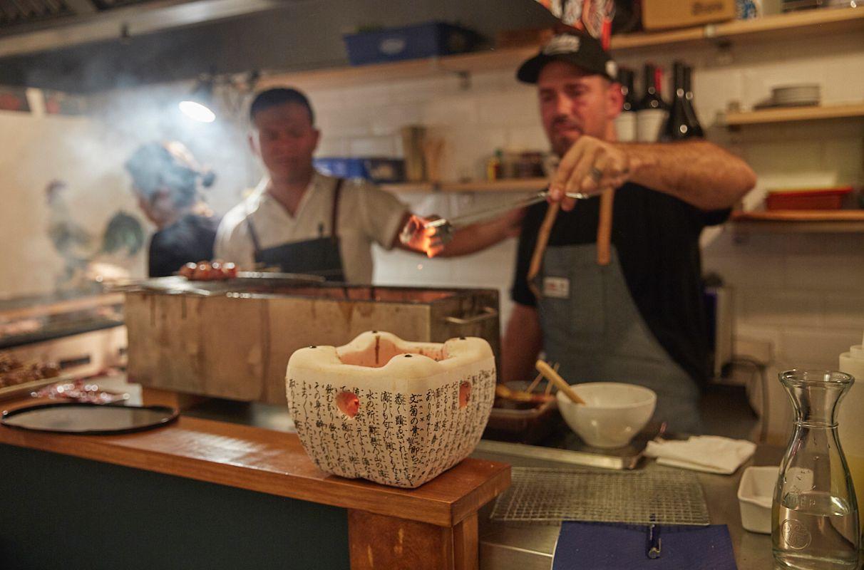 El chef Aitor Olabegoya echa ascuas en un recipiente de cocina japonesa en el restaurante pop up, en Poble Sec (Barcelona).
