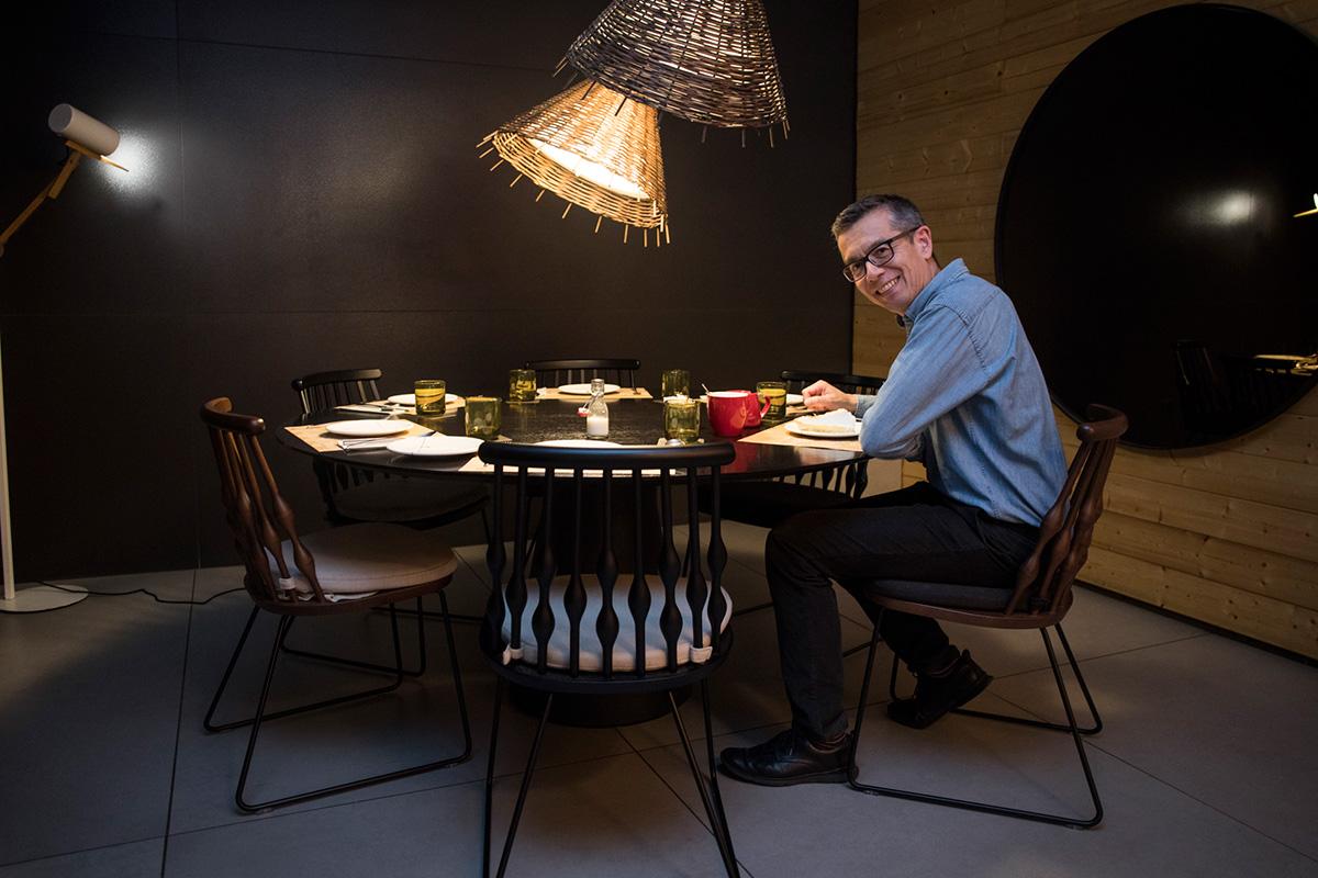 El chef anglo-birmano Steve Anderson posa sentado en las sillas de su local.