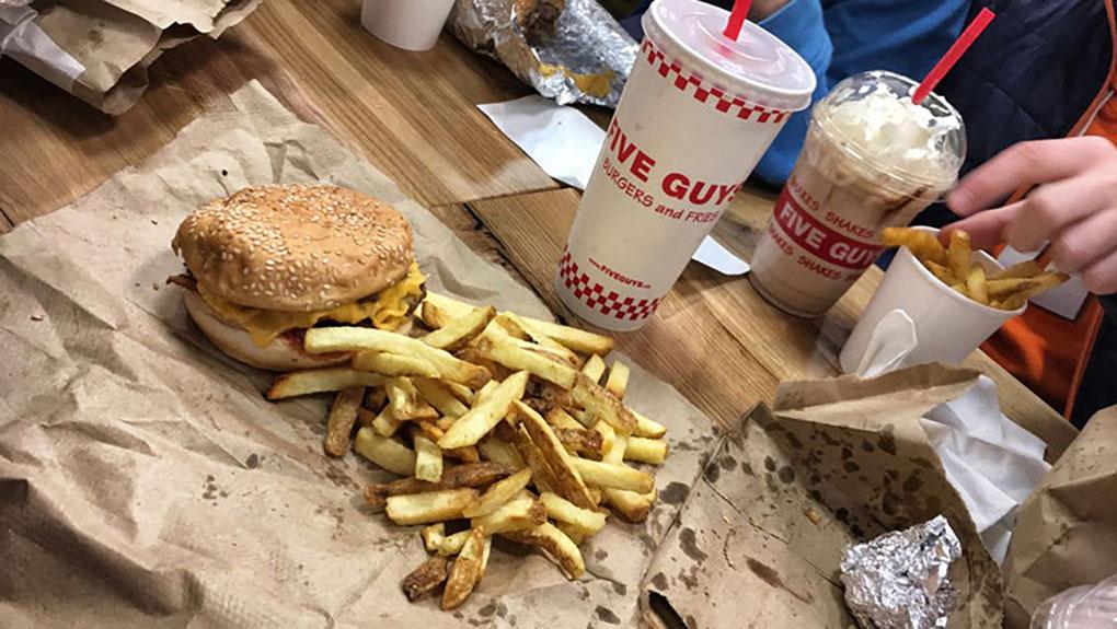 La hamburguesa y las patatas junto a un refresco y un batido.