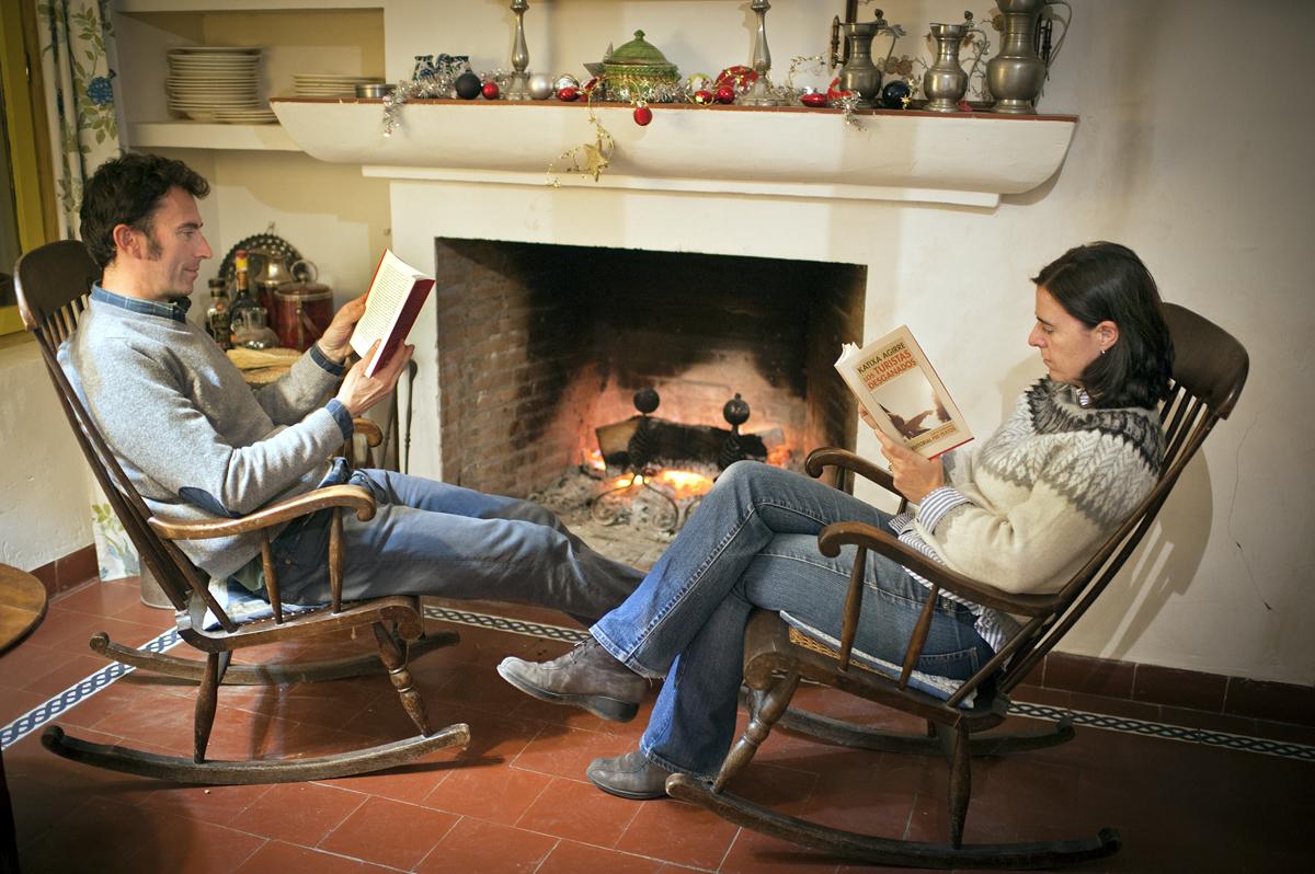 Pareja leyendo junto a la chimenea