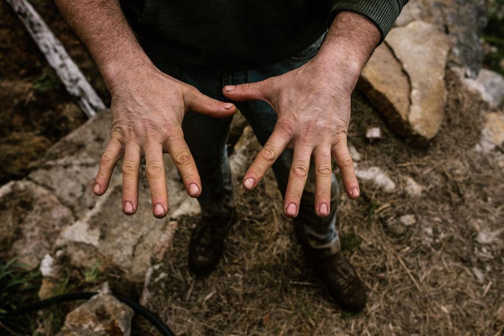 Manolo muestra sus manos ajadas y cubiertas de tierra, prueba del duro trabajo que requieren las fincas.